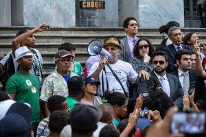 Frei Gilvanderson Luís Moreira, ao lado da comissão de advogados que representou a ocupação no processo do TJMG, anuncia a decisão que autoriza a reintegração de posse da área ocupada pelas forças policiais. Fotografia: Lucas D'Ambrosio